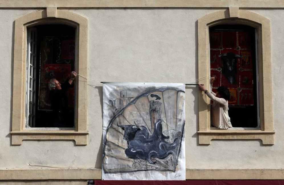 Las personas tienen una bandera que representa a un torero y un toro...