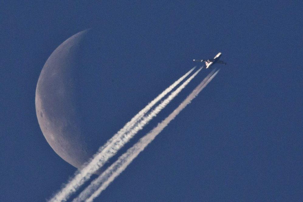 Un avión sobrevuela Nüremberg (Alemania) con la luna de fondo.