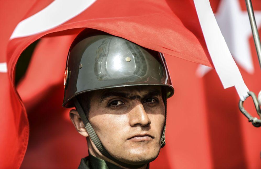Una bandera turca  cubre parcialmente el rostro de un soldado Turkish...