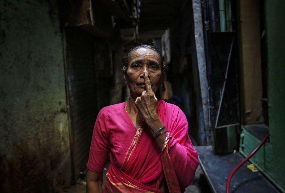 Una mujer muestra su dedo marcado de tinta después de votar en un...