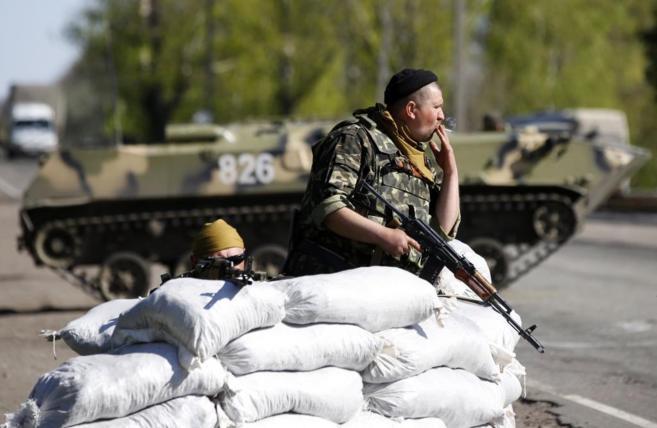 Un soldado ucraniano fuma un cigarrillo en un puesto de control al...