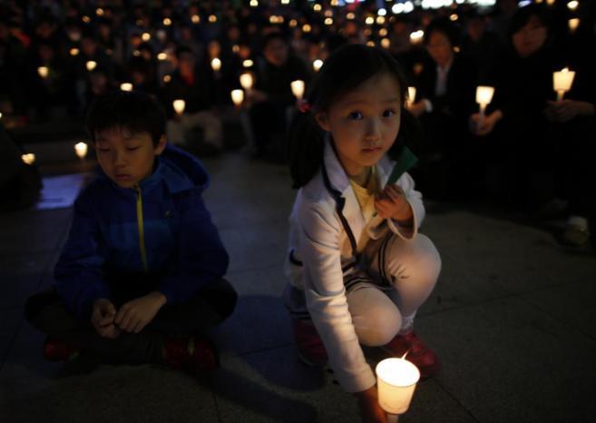Una niña surcoreana participa en una vigilia por las víctimas del...