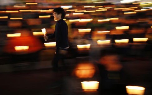 Un joven surcoreana participa en una vigilia por las víctimas del...