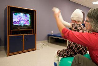 Un niño con varios vendajes juega ante una pantalla con su madre