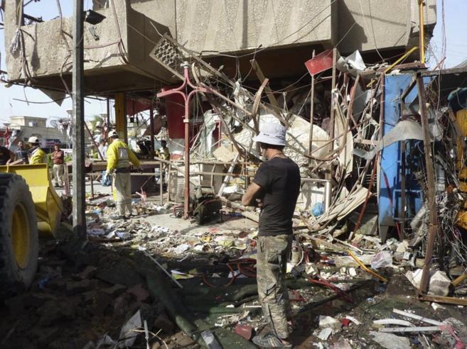 arios iraquíes observan el lugar donde ayer se llevó a cabo un...