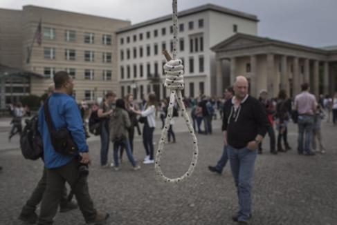 Turistas frente a una soga colocada en Berlín por exiliados iraníes...