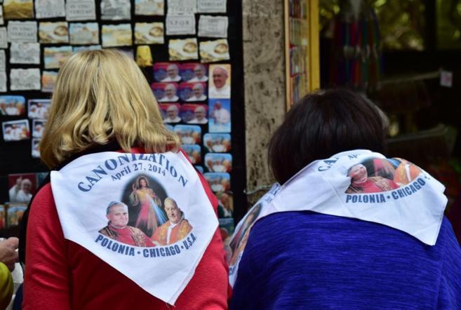 Dos mujeres con pañuelos de la canonización miran una tienda de...