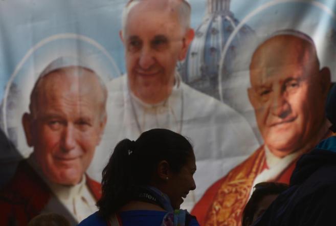 Una mujer se siluetea frente a un cartel que muestra a Juan XXIII...