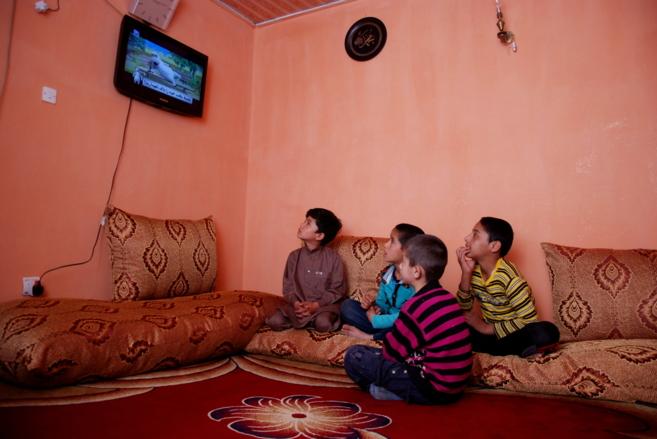 Niños afganos ven la televisión en Kabul.