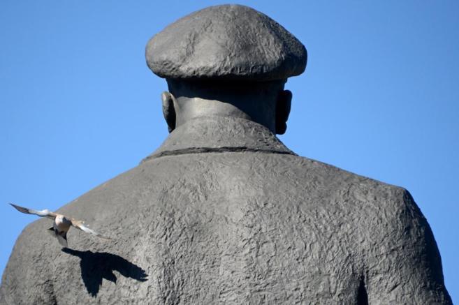 Una paloma vuela junto al monumento a Lenin, en Slaviansk (este de...