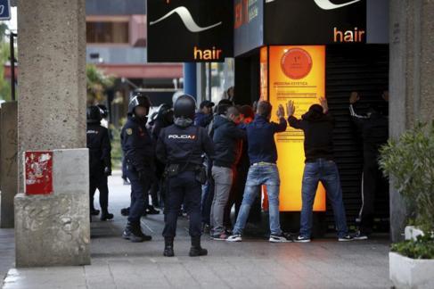Un agente vigila a varias personas a las que retiene.