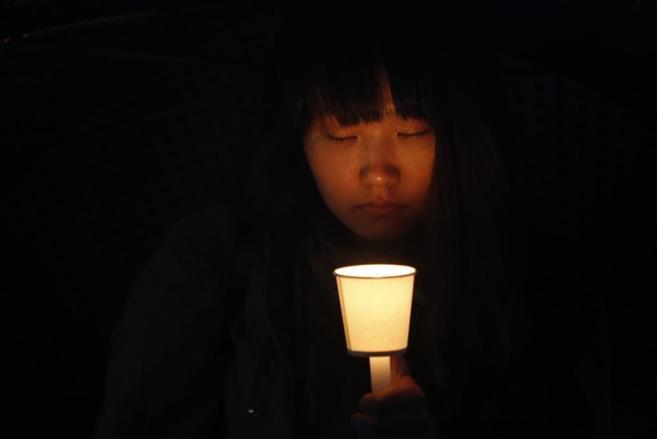 Una joven surcoreana reza por estudiantes fallecidos en el naufragio...
