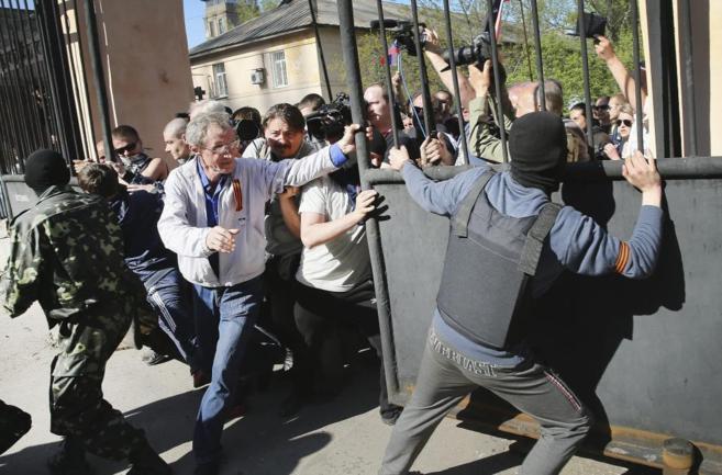 Activistas prorrusos bloquean la entrada a la televisión de Donetsk.
