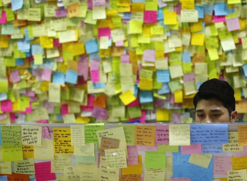 Un hombre lee uno de cientos mensajes de ánimo en un 'muro de...