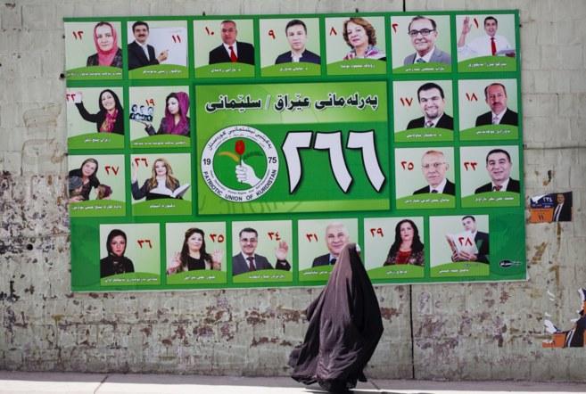 Una mujer ante un cartel electoral  de la Unión Patriótica del...