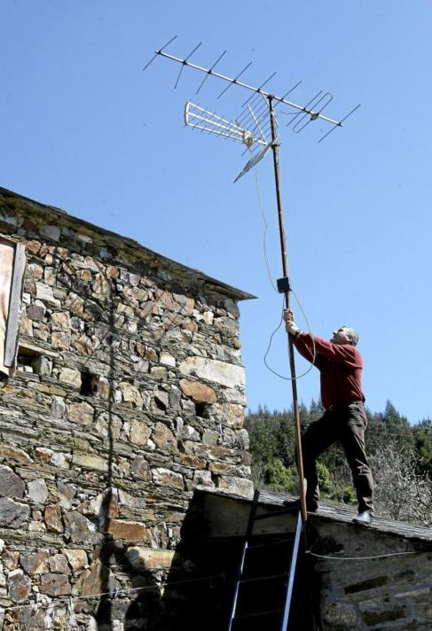 Un antenista orienta el receptor de una casa de la localidad lucense...