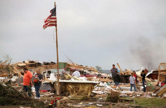 Un grupo de vecinos examina la zona devastada donde estaban sus...