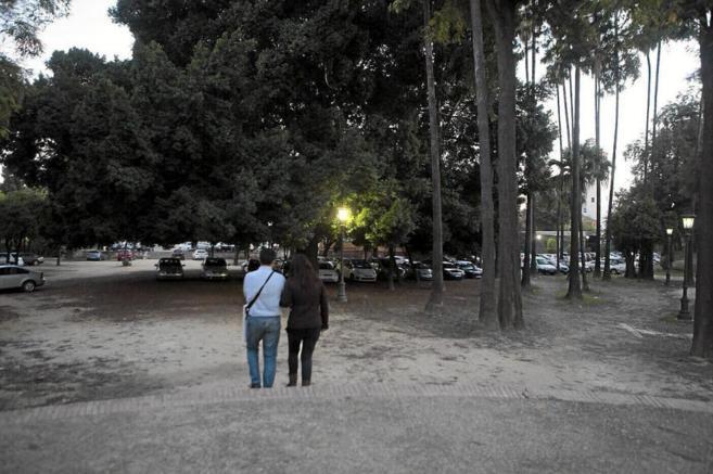 Una pareja pasea por un parque de Sevilla.