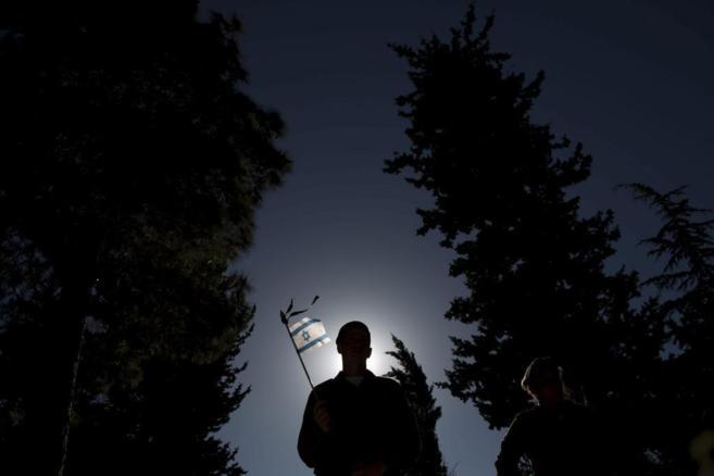 Un soldado israelí sostiene una bandera en el cementerio militar...