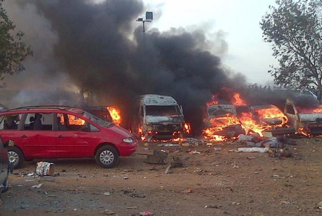 Varios coches arden tras la explosión.