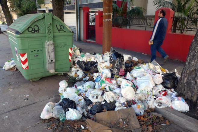 Un hombre pasa junto a uno de los montones de basura que hay en las...
