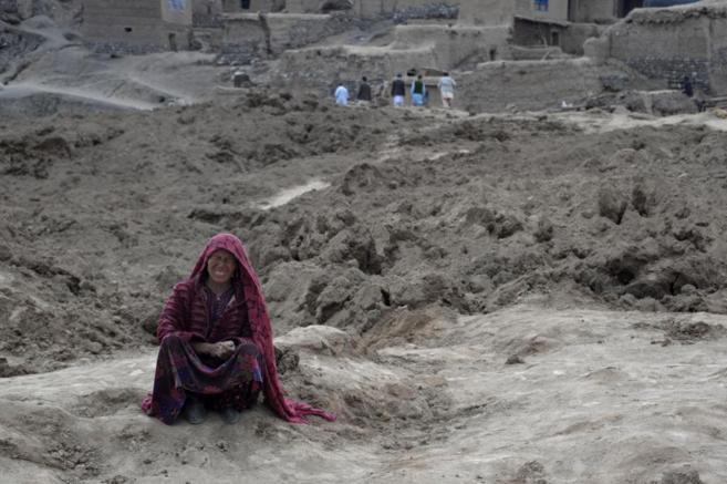 Una mujer afgana llora sentada en una montaña de barro tras el...