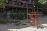 Árbol derribado junto a un parque infantil obsoleto.