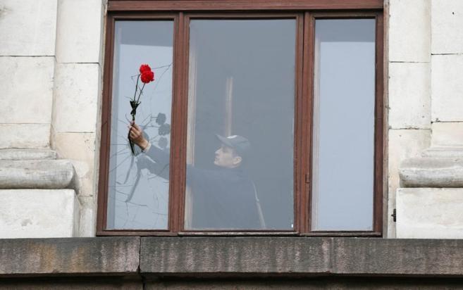 Un hombre coloca flores en una ventana del edificio incendiado en...