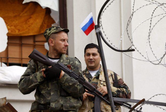 Rebeldes prorrusos hacen guardia en la puerta del edificio del...