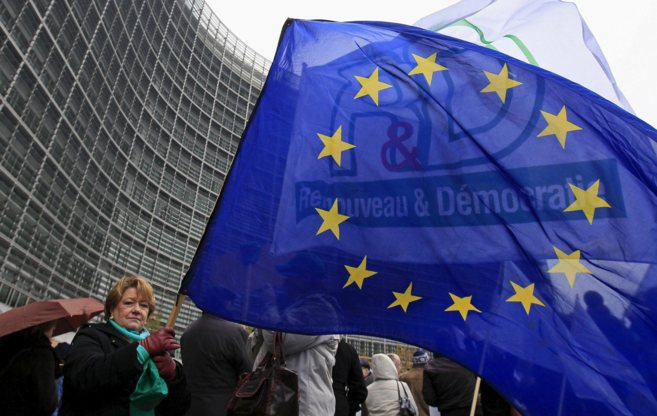 Una funcionaria comunitaria en huelga agita una bandera de la UE en...
