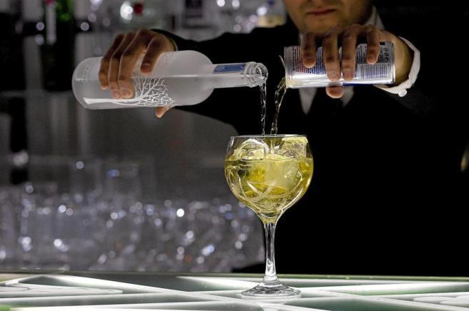 Un camarero mezcla en una copa licor de una botella y el contenido de...