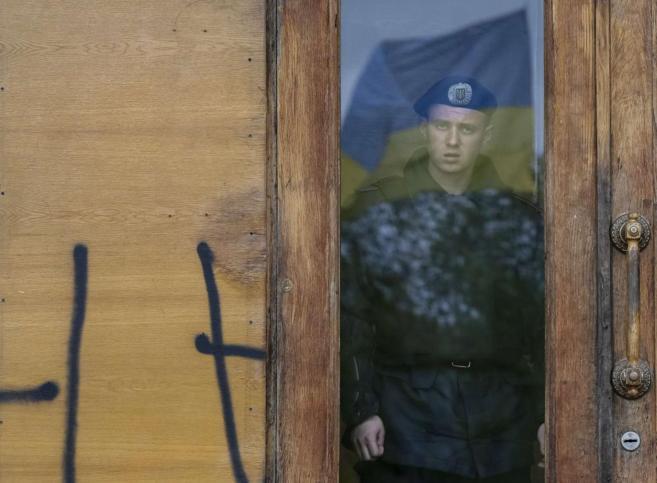 Un policía mira a través de una ventana de la sede del Gobierno...