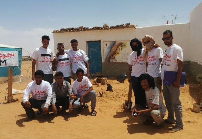 Jóvenes saharauis ante una reproducción del muro en el Festival de...