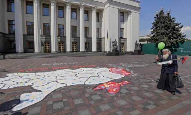 Un anciano observa un mapa de Ucrania, con los territorios en disputa...