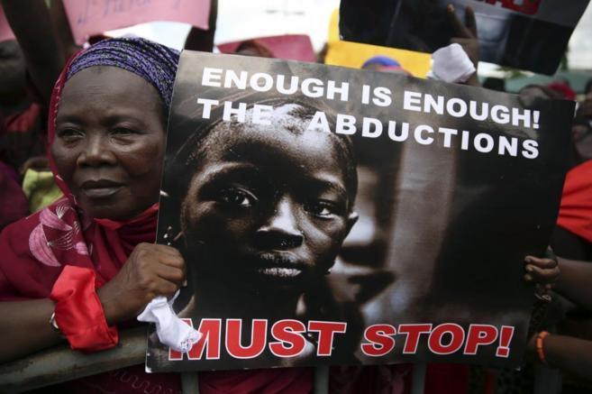Una manifestante en Lagos muestra un cartel pidiendo el fin de los...