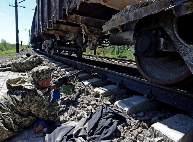 Militantes prorrusos toman posiciones junto a una vía de tren en...