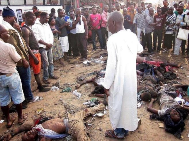 Los transeúntes miran los cadáveres de las víctimas de un ataque...