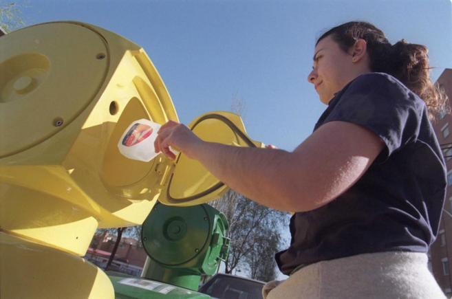Una mujer tira un envase al contenedor amarillo