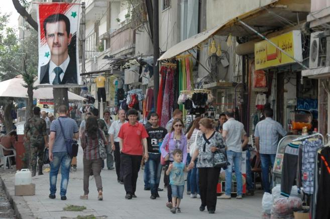Ciudadanos sirios pasan junto a un cartel de Bashar Asad en un...