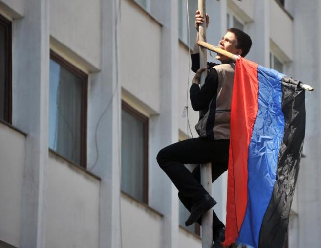 Un joven prorruso intenta colocar una bandera de la autoproclamada...