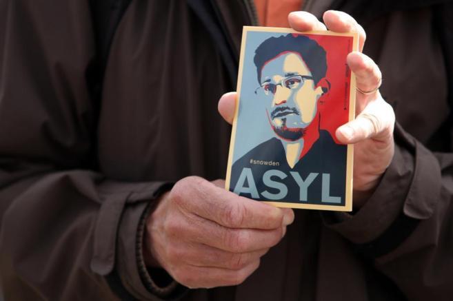 Una manifestante en una protesta a favor de Edward Snowden muestra su...