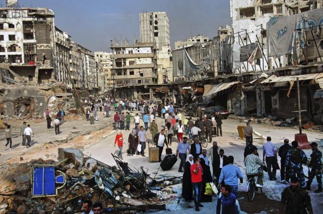 Decenas de civiles caminan por el casco antiguo de la ciudad de Homs,...