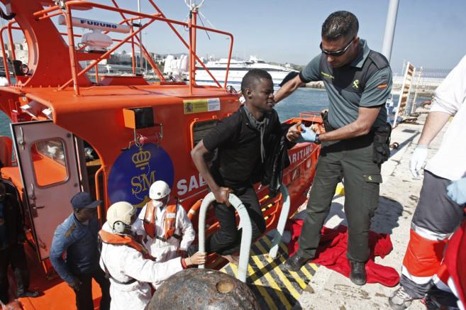 Un agente de la Guardia Civil ayuda a los inmigrantes rescatados a...