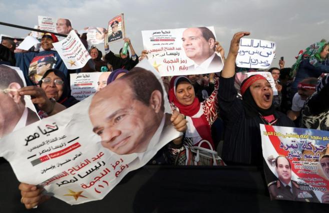 Seguidores de Al Sisi muestran posters de su campaña en el acto de...