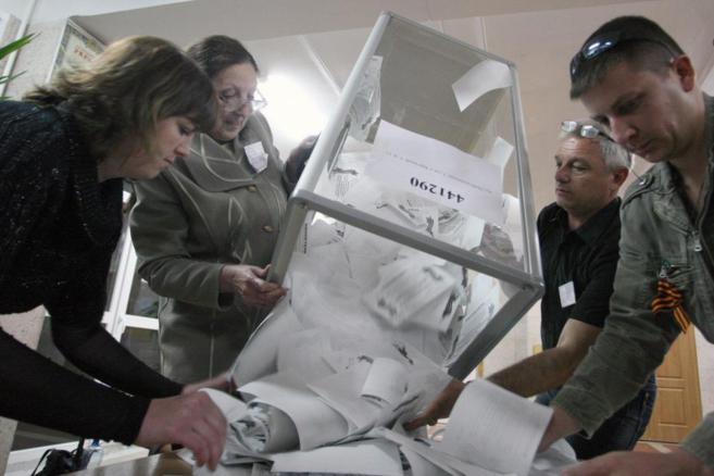 Los miembros de una comisión electoral cuentan los votos después del...