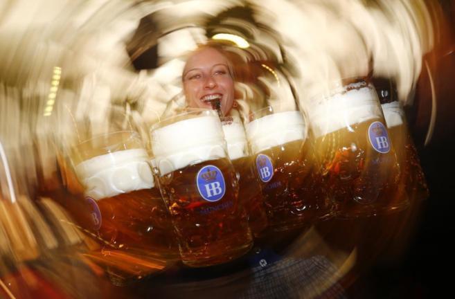 Una camarera lleva varias jarras de cerveza