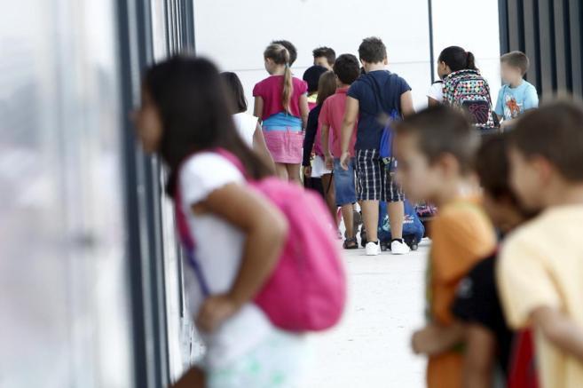 Niños entrando en un colegio.