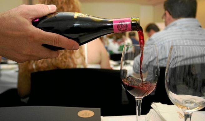 Un sumiller sirve una copa de vino tinto.
