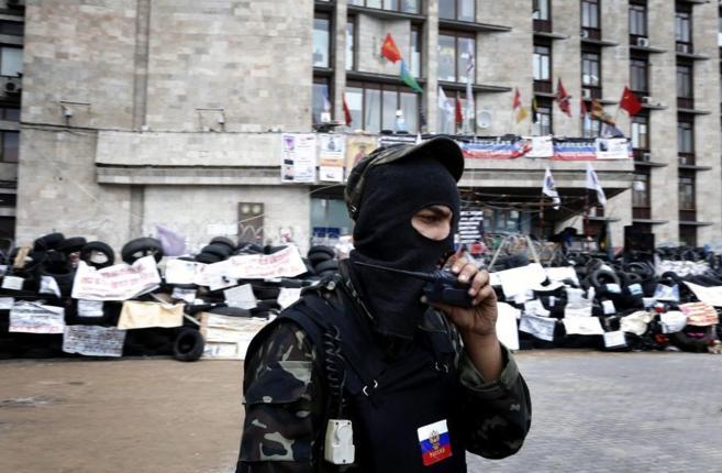 Un partidario de la República Popular de Donetsk camina frente a una...