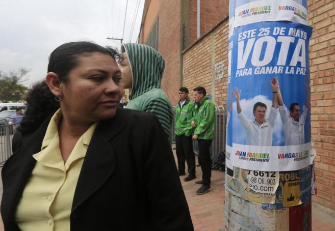 Una seguidora de Juan Manuel Santos mira un cartel electoral en...